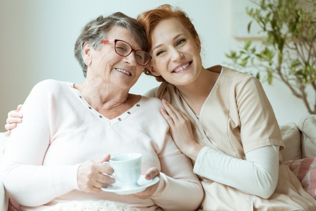 Smiling elderly lady drinking tea with younger lady